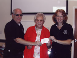 Kath presenting a cheque to Colin and Libby
